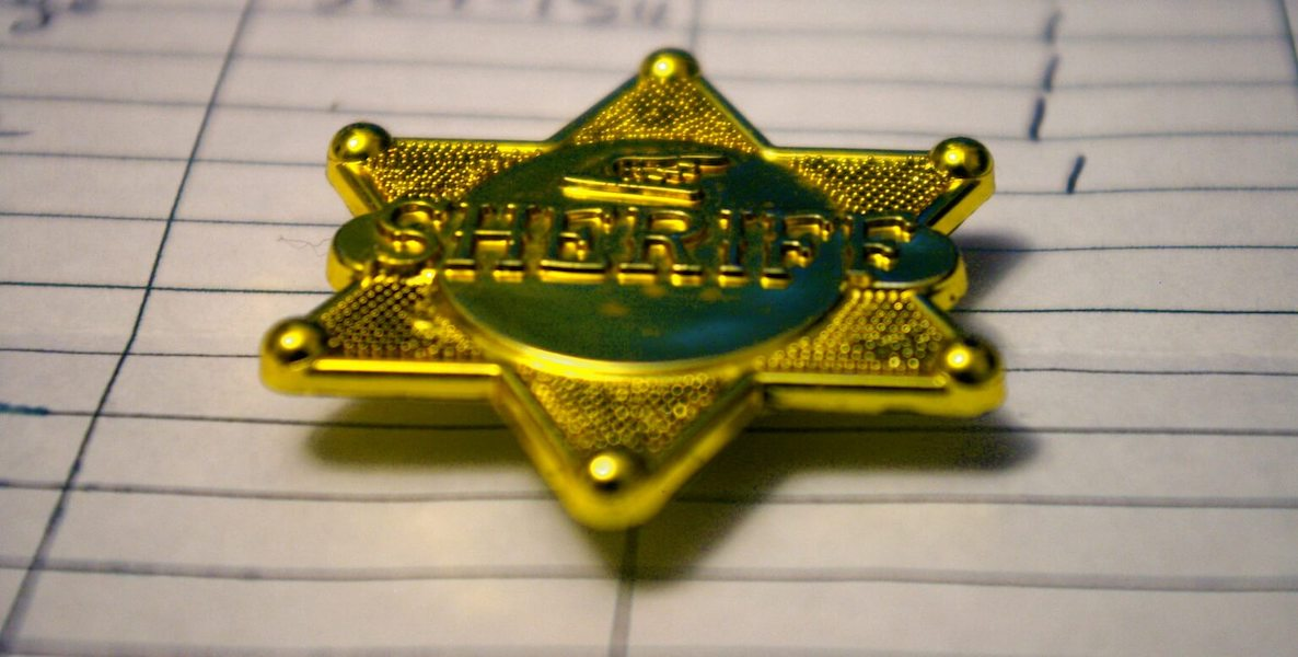 A sheriff's badge lays on a piece of paper.