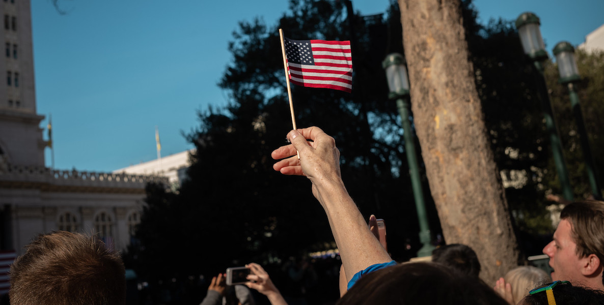 A citizen waves an American flag in the air.