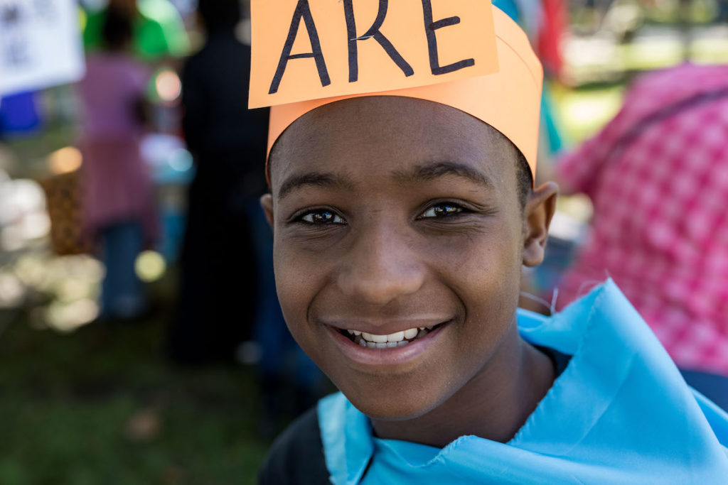 """A kid attends Mighty Writers writing festival, wearing a sign on his head that says, """"Are."""""""