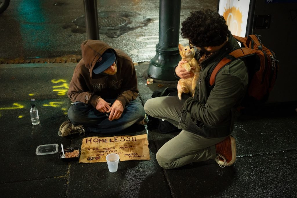 A man stops to play with a homeless man's cat on a rainy night in the city.
