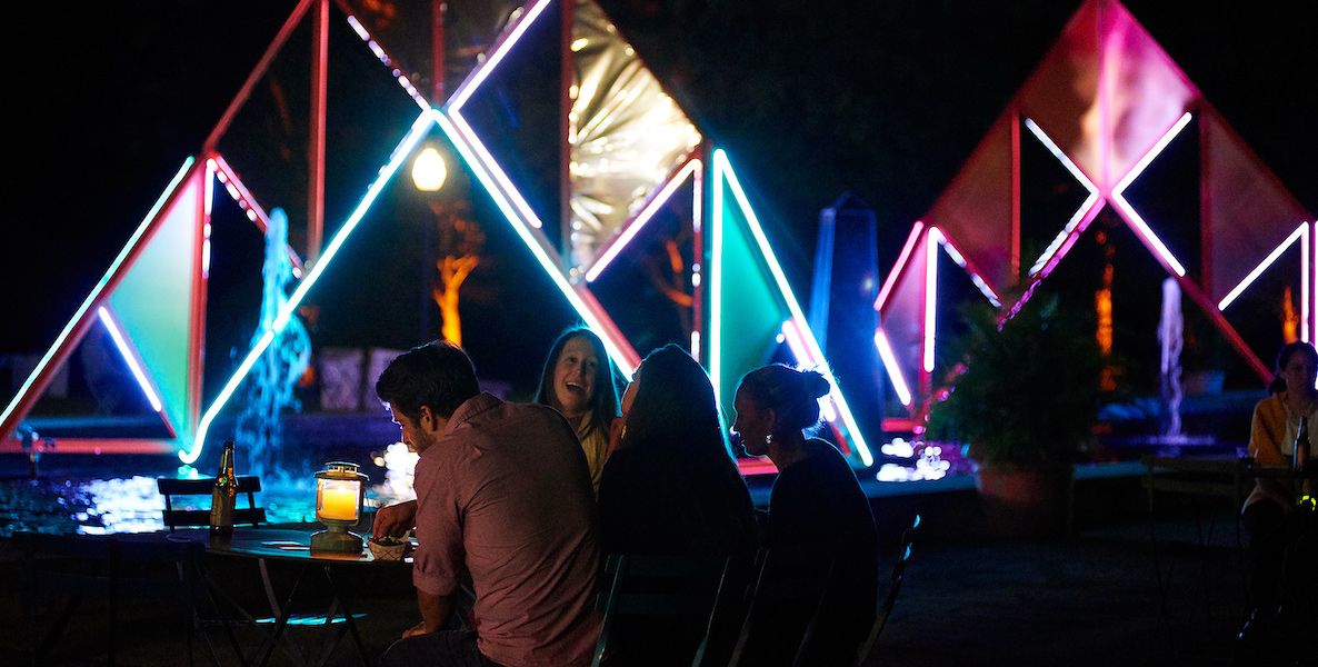 People gather together at GLOW in the Park, with an illuminated display in the background.
