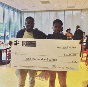 Two smiling students hold a large check for $1,000.