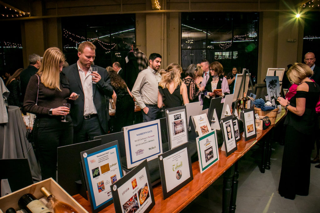 People gather around a silent auction at the annual An Evening With Emily's Entourage Gala