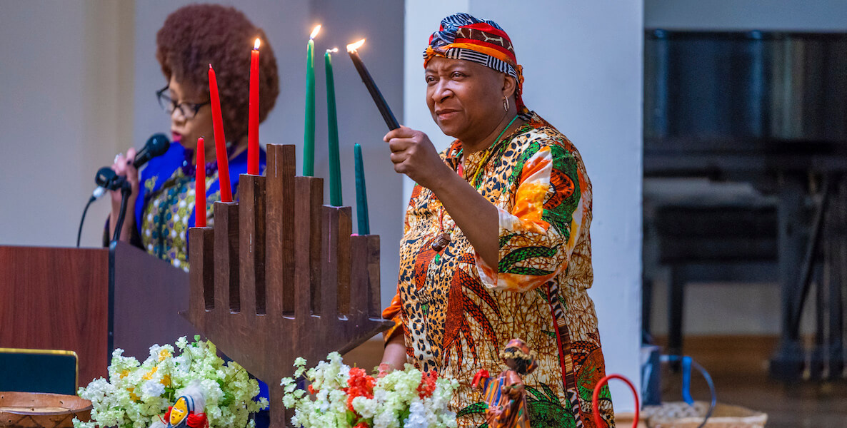 A woman lights Kwanzaa candles at the annual celebration at the African American Museum in Philadelphia
