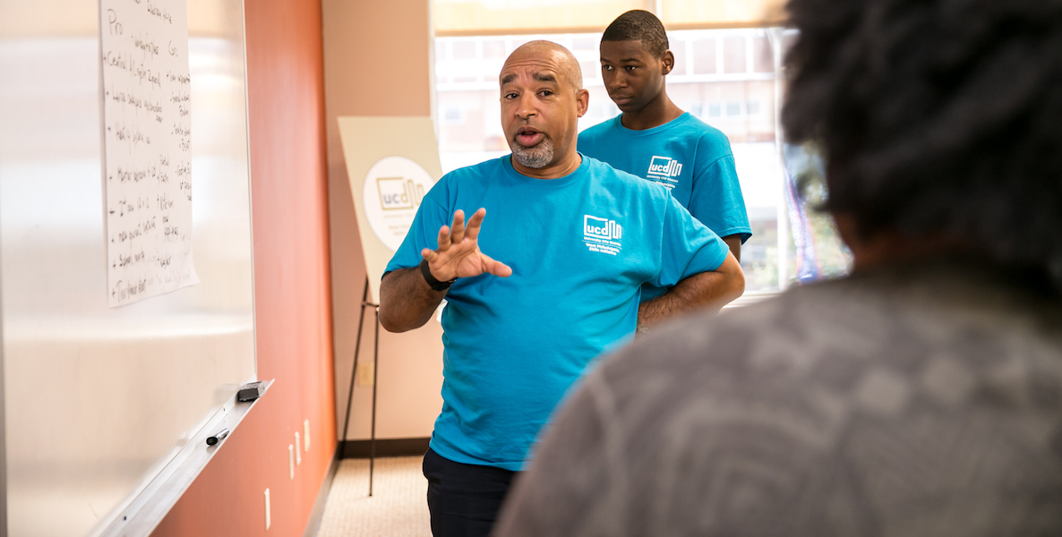 A teacher from the West Philadelphia Skills Initiative stands in front of a dry erase board explaining something to a student.