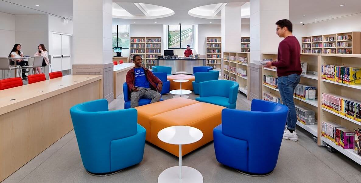 Youth lounge around a brightly lit and colorful Field Teen Center, located in the basement of the Central Parkway Branch of the Free Library of Philadelphia.