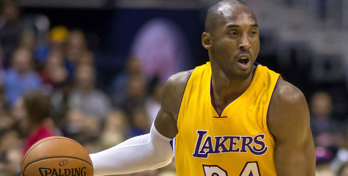 Kobe Bryant dribbles a basketball in his Lakers jersey.