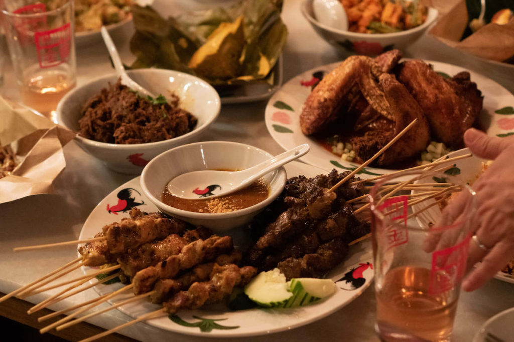 A spread of food at Sate Kampar in South Philadelphia, includes lots of meat skewers