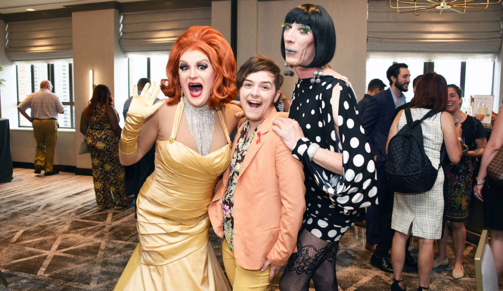 Two kooky drag queens greet a well-dressed guest at Action Wellness's annual Glamsino Royale event.