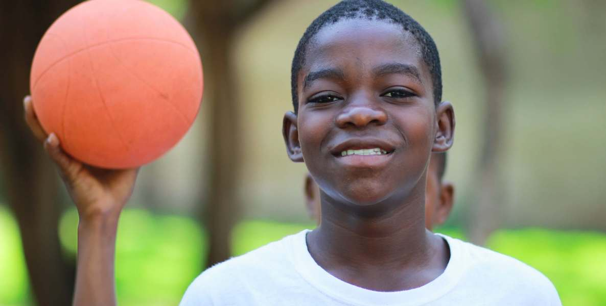 A kid holds up a basketball and stares into the camera.