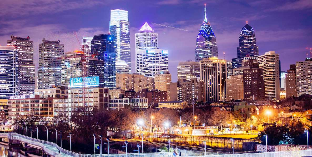 Photo shows the glowing Philadelphia skyline at night, a view from the southwest of the city.