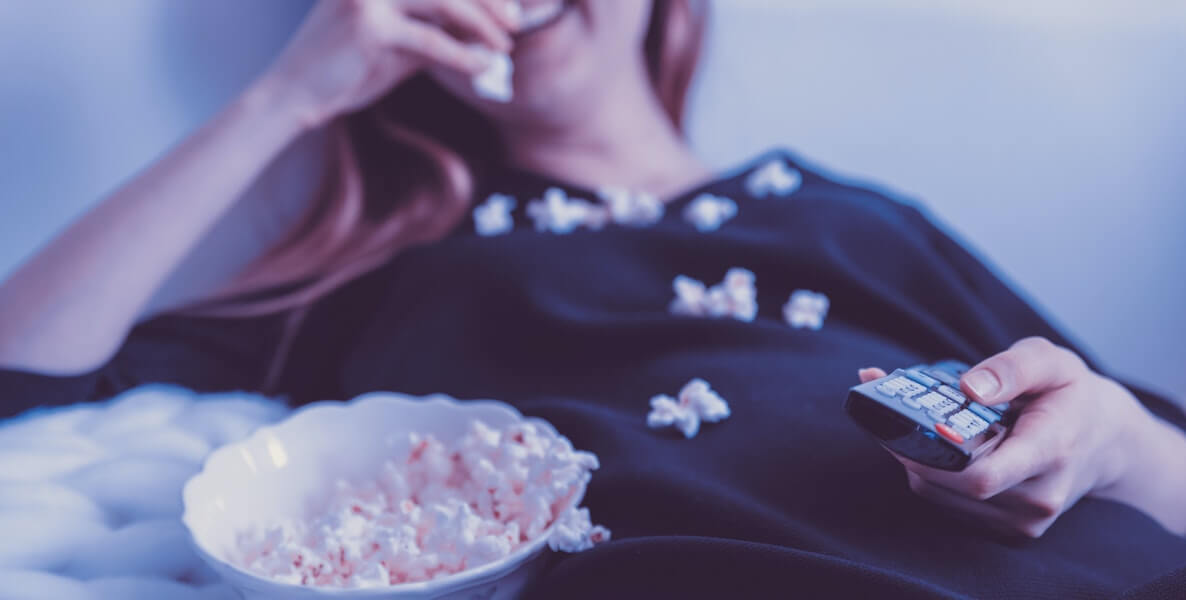 A woman lays back and watches a funny movie during her coronavirus quarantine—with popcorn in hand!