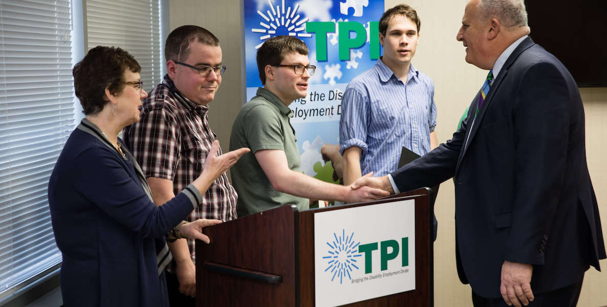 Graduates from The Precisionists, a company that readies people with autism for jobs in which they'll thrive, shake hands with a potential employer.