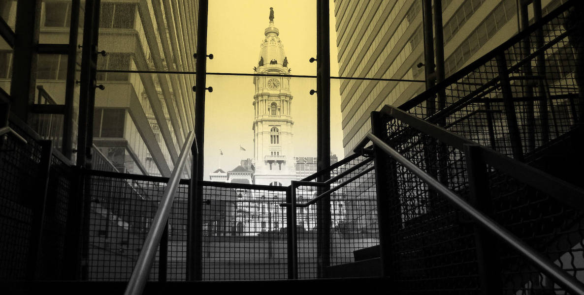 An image of City Hall in Philadelphia, through a yellow glass tunnel leading to suburban station.