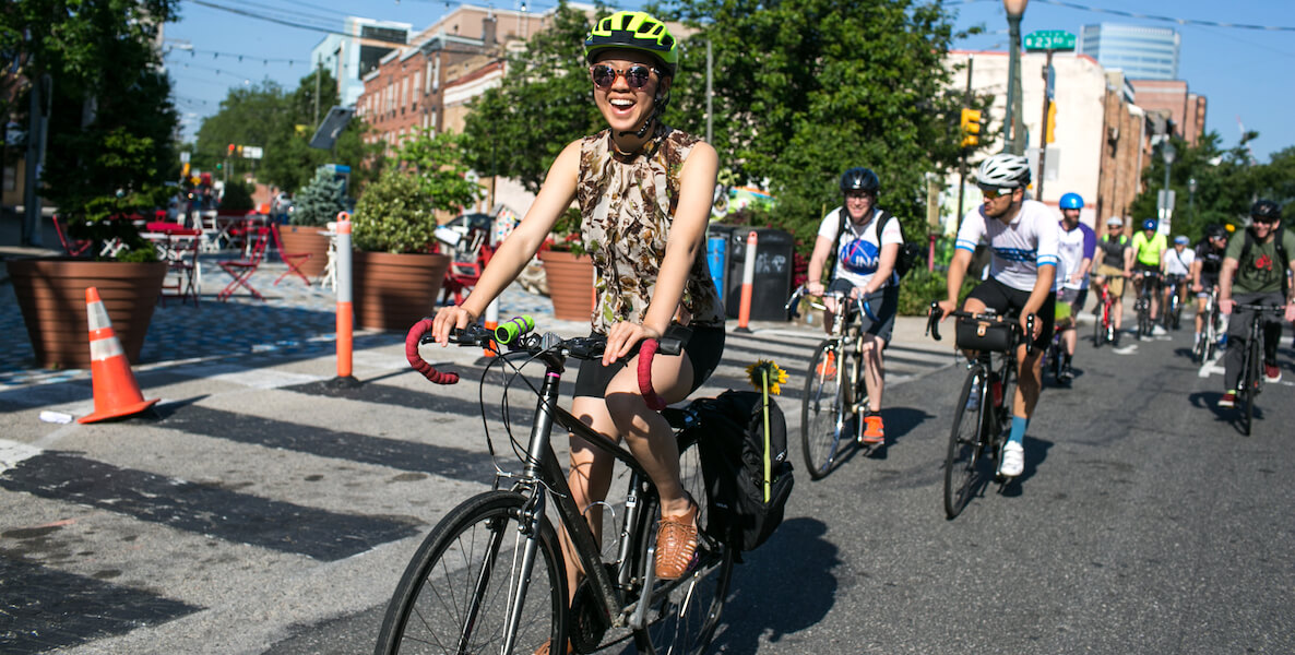 A woman rides through South Philadelphia on her bicycle, smiling big with a helmet on.