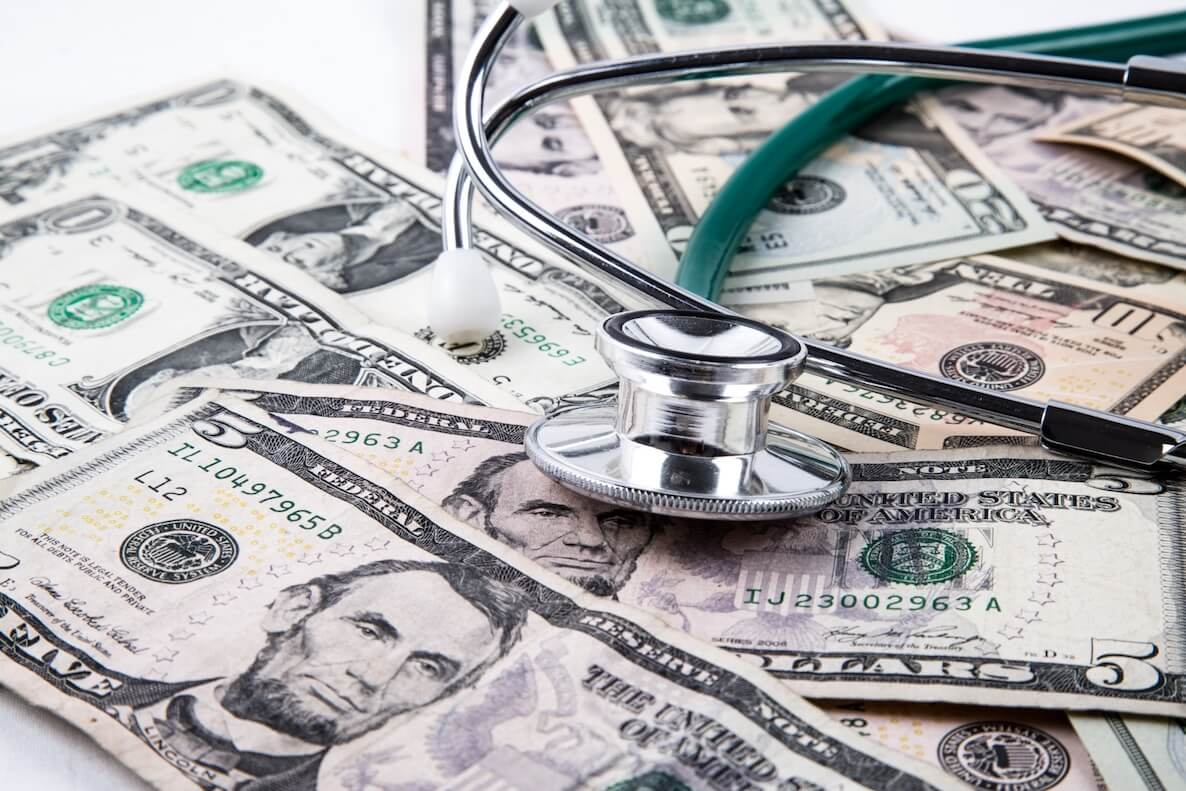 stethoscope on pile of money, cost of healthcare
