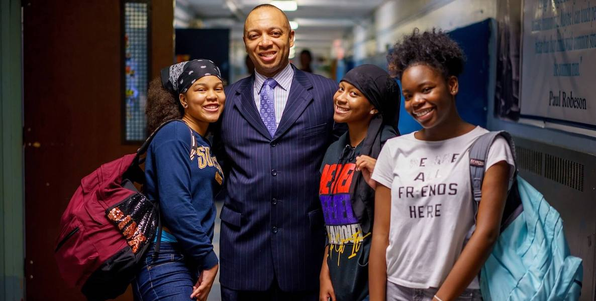 Richard Gordon, principal of Philadelphia's Robeson High School, poses with students in the hallway.