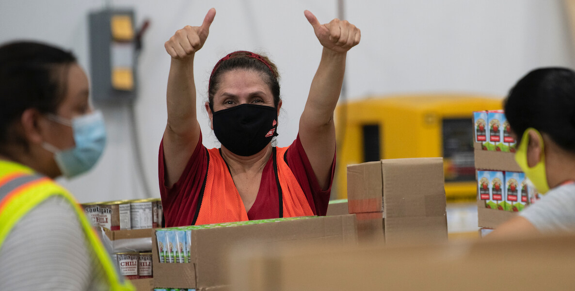 A small business factory worker wearing a mask during Covid-19 gives a thumbs up during the pandemic