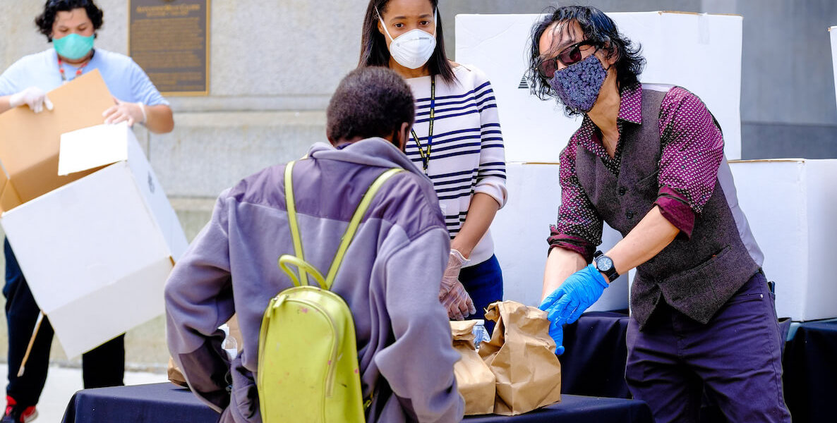SEAMAAC Executive Director Thoai Nguyen hands out food at City Hall during the coronavirus pandemic