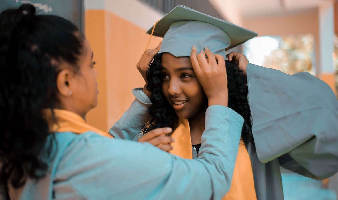 Two women help each other put on their graduation hats before the ceremony