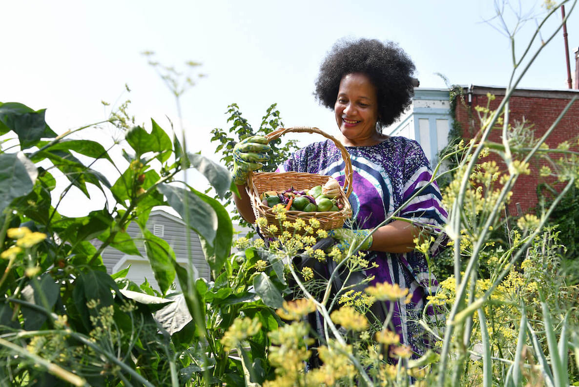 A Philadelphia garder shows off a bounty of produce that she grew in her urban garden, beautiful yellow flowers frame the screen in the foreground.