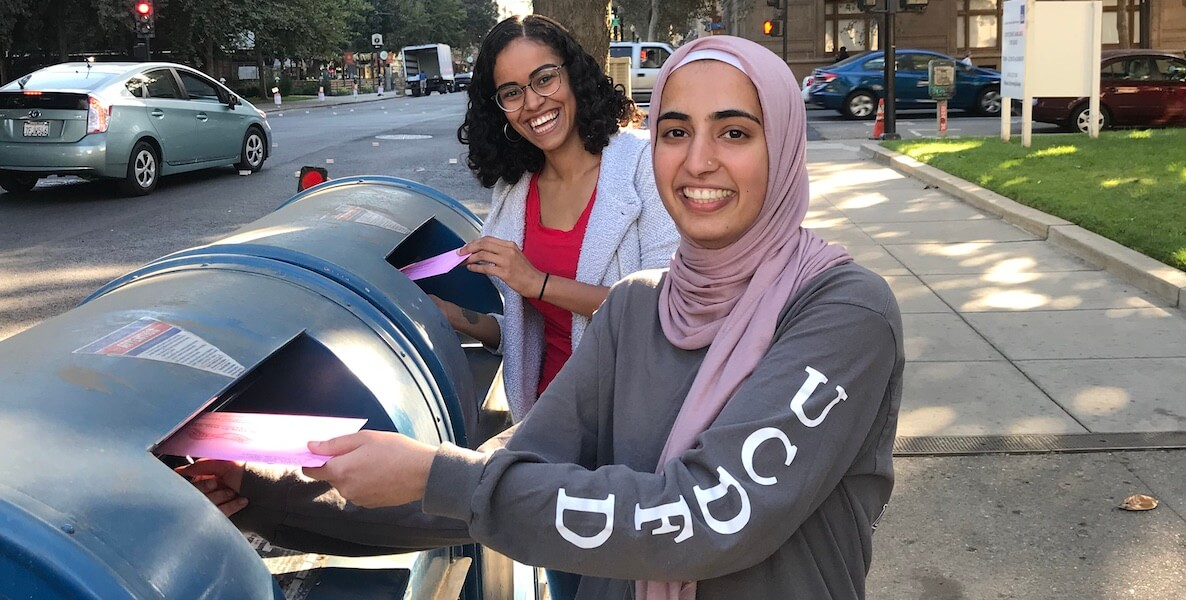 Two women drop their ballots in the mailbox before Election Day 2020