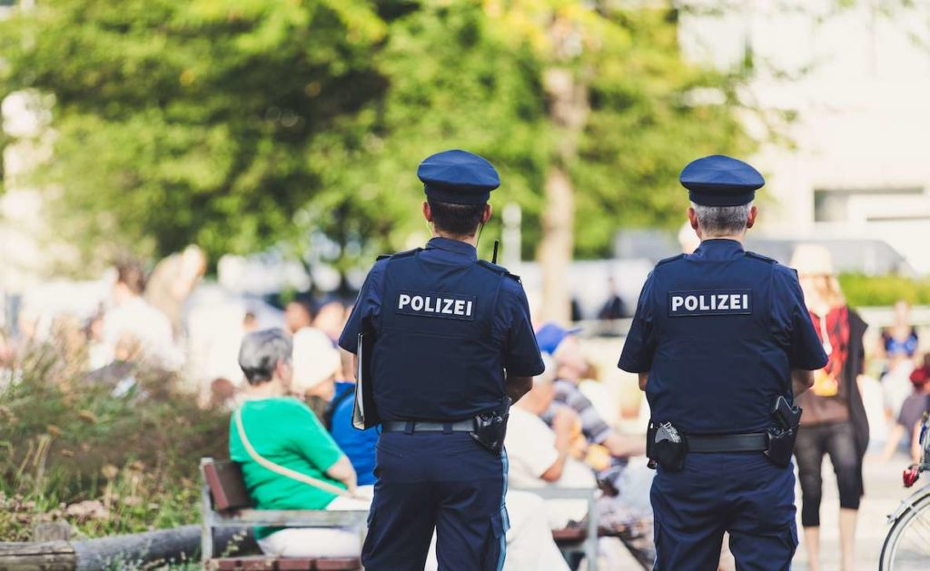 "Two German cops have their back turned to the camera. Their shirts read ""polizei"""