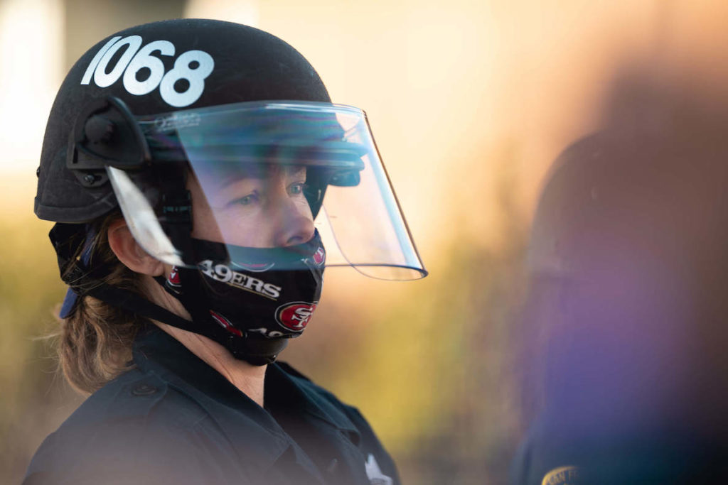 A female police officer wears a 49ers mask in San Francisco