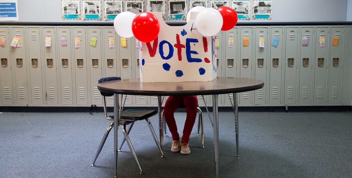 Someone sits behind a hand-painted vote sign with balloons attached.