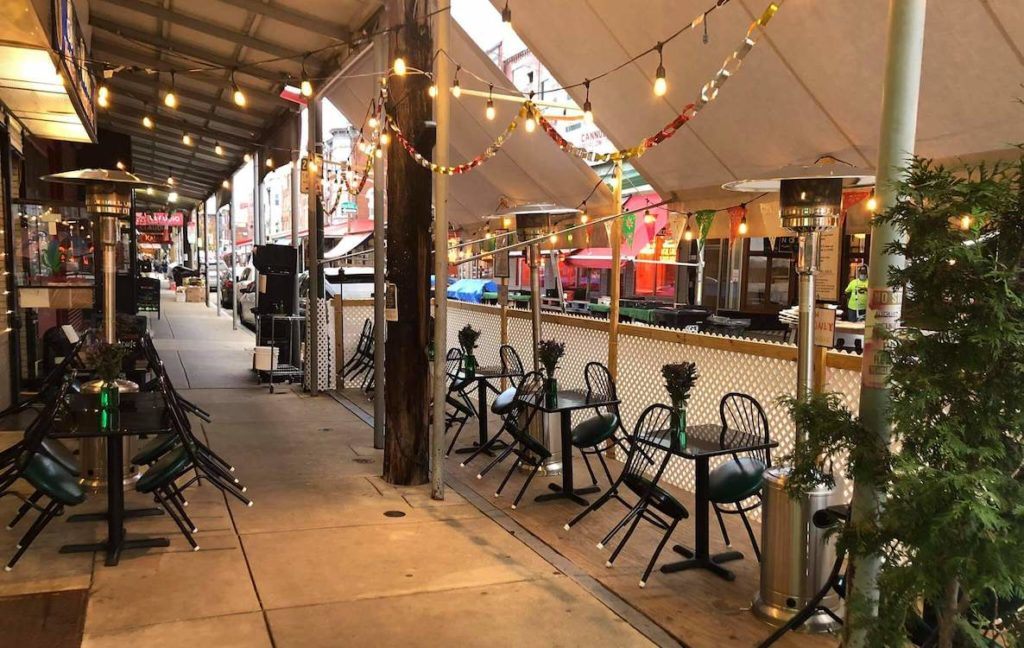 The outdoor dining area at Italian Market Mexican restaurant Blue Corn, decorated with hanging lights and heat lamps