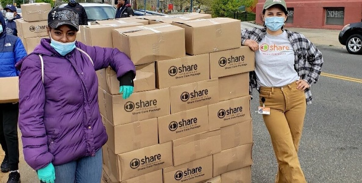 A woman hands out food donations to people in need.