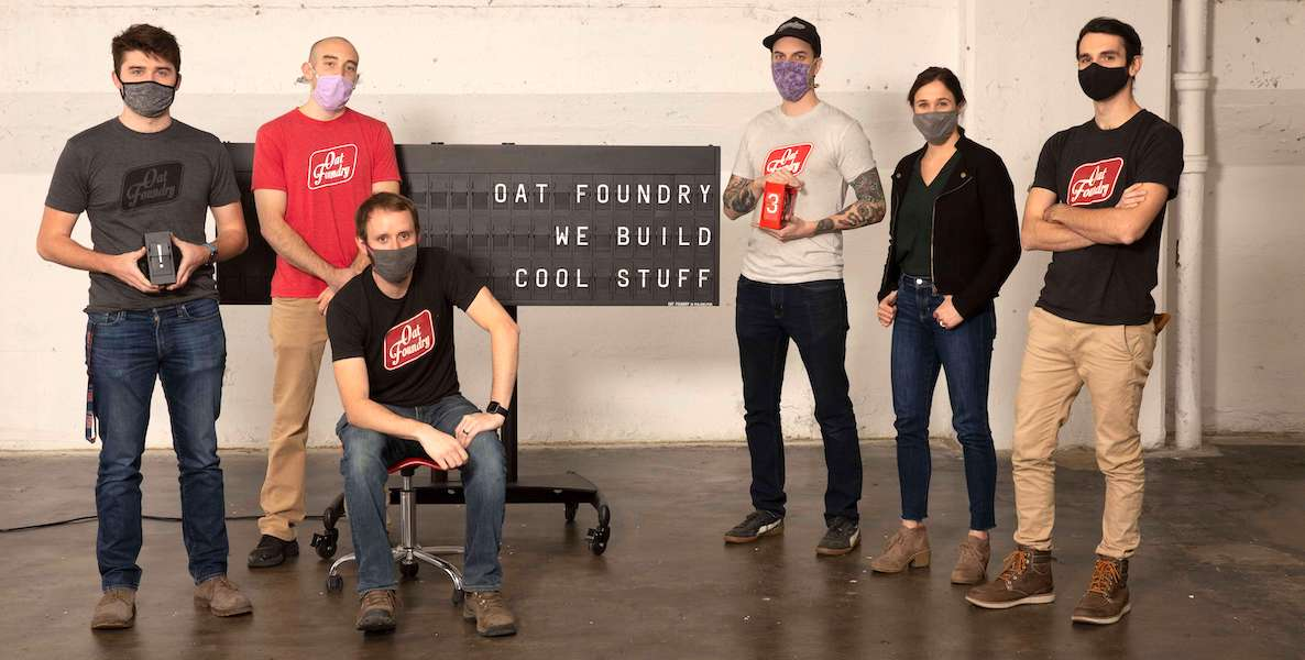 "Oat Foundry employees stand next to a sign that says ""We build cool things."""
