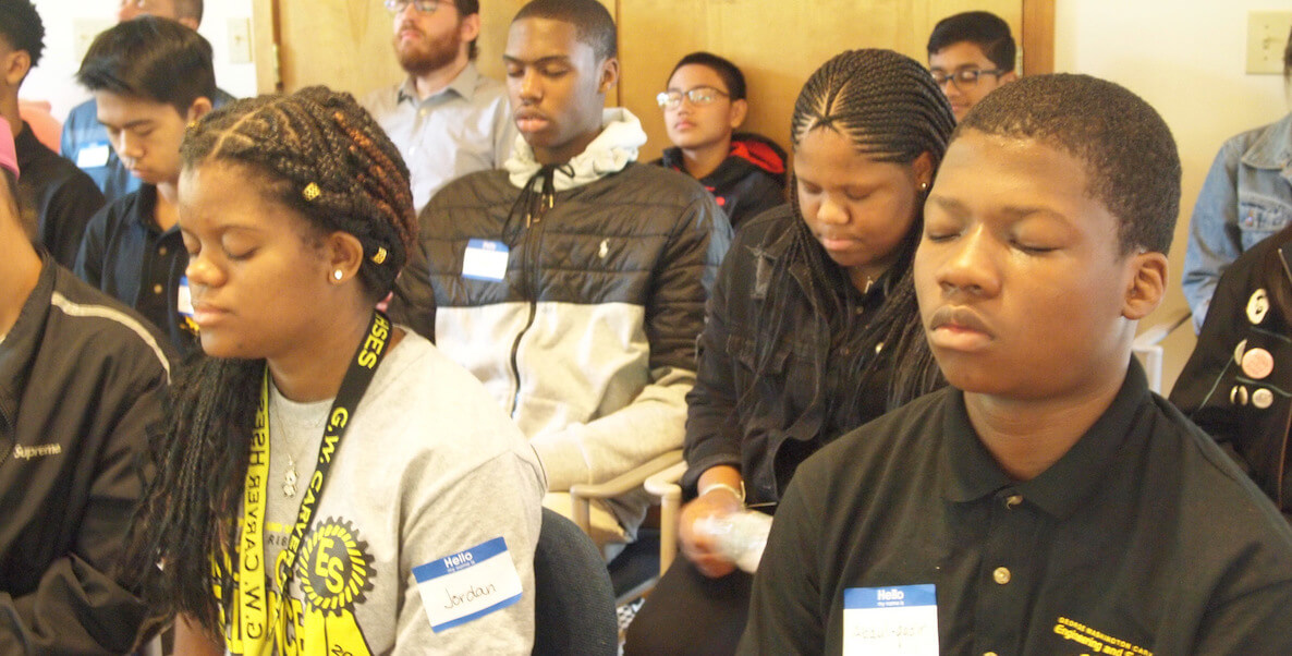 Students of color meditating in classroom