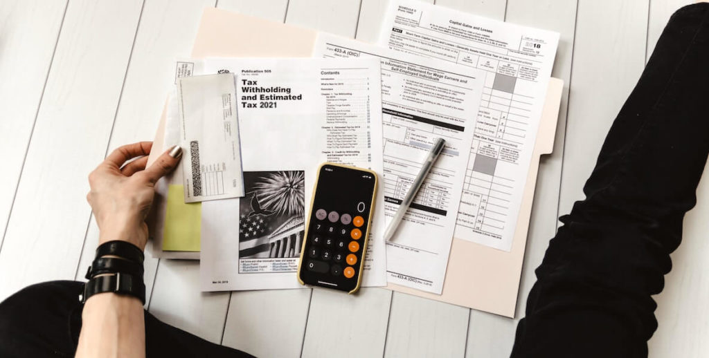 A person sits on the floor with a calculator and papers spread all over the place trying to do her taxes