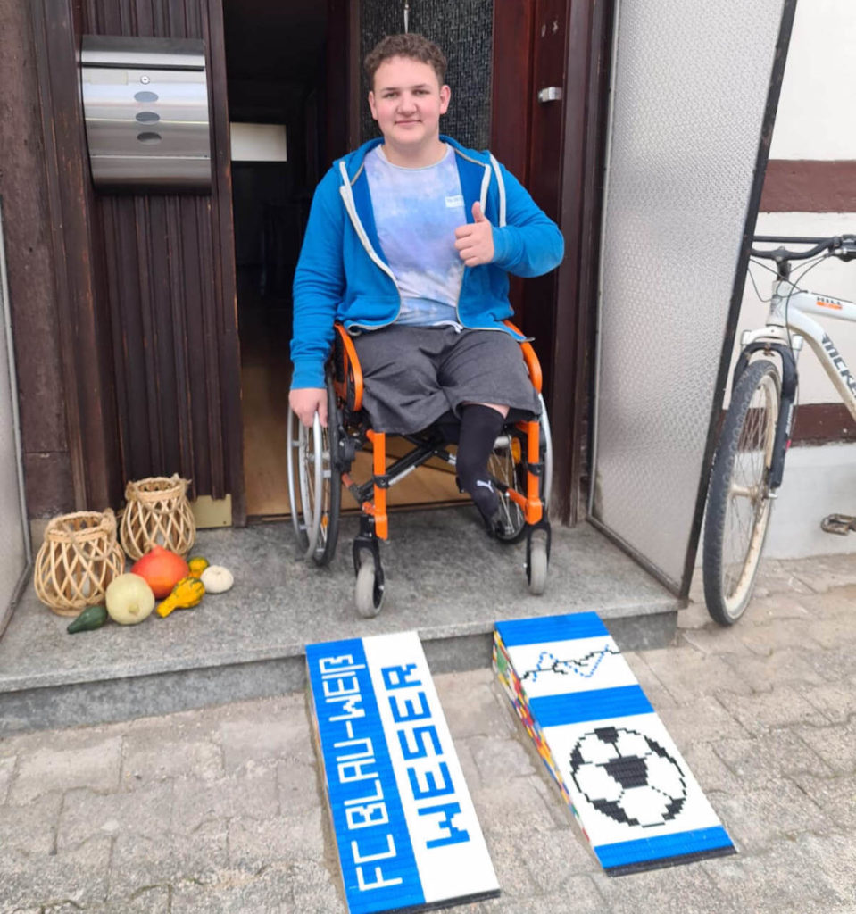 A young man thumbs up his LEGO ramps outside his home
