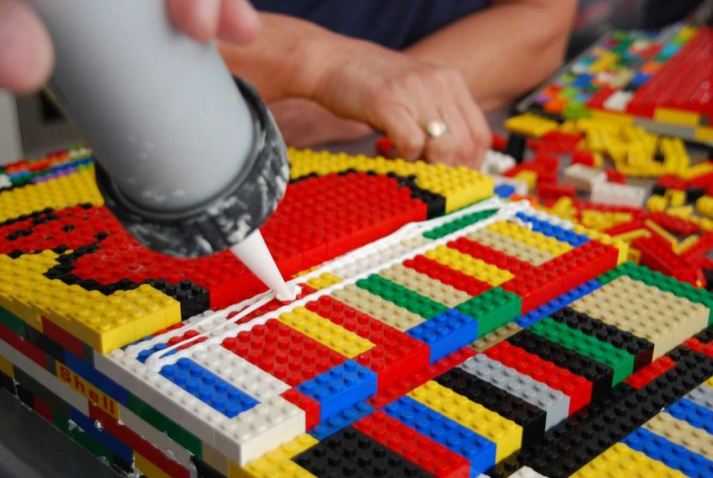 Rita Ebel uses glue to secure the pieces on her LEGO ramp