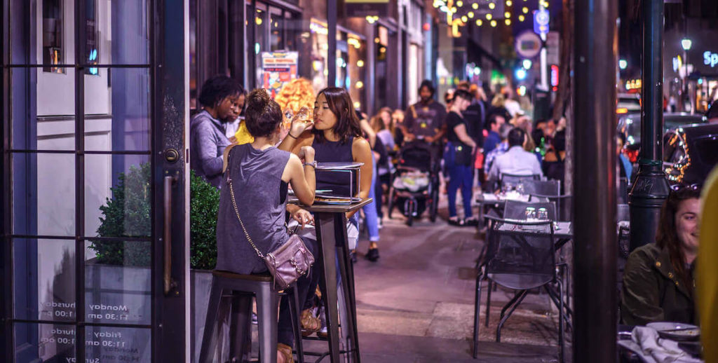 Diners eat on outdoor tables along 13th Street in Midtown Village