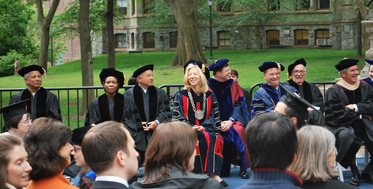 Penn president Amy Gutmann walking across the stage in a cap and gown, watching the commencement procession